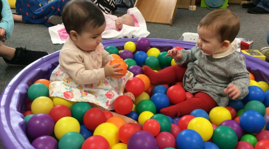 2 babies in a ball pit playing