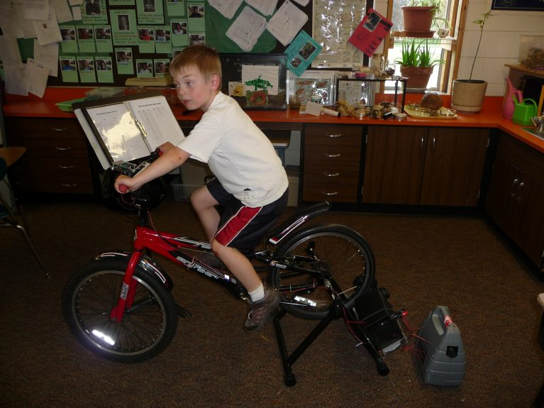 A boy uses a stationary bike to generate power