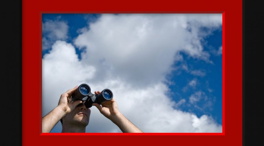 Person looking through binoculars at the sky
