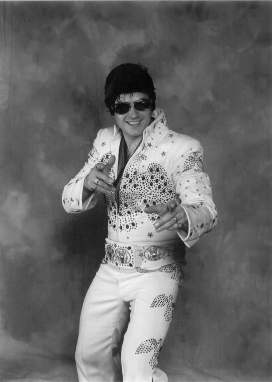 A man pretending that he's Elvis, despite the fact that he is not Elvis