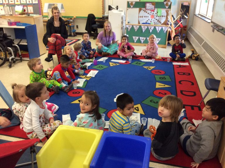 Preschoolers having a break with teachers