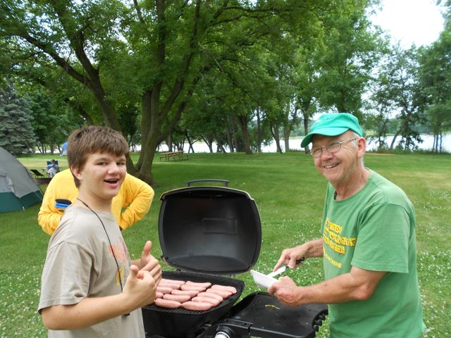 An older gentleman and a young boy stand smiling at the camera as they grill a multitude of hotdogs on a large grassy swath of land along the banks of the Canon river.