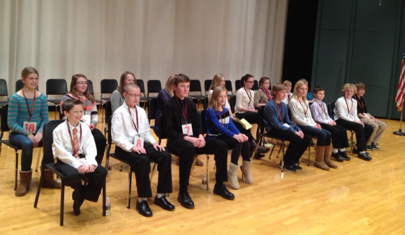 Students sit smiling as they await their turn to step up to the podium and spell a word at a spelling bee.