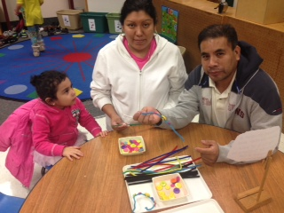 young Hispanic family (mom, dad and child) attending Family School