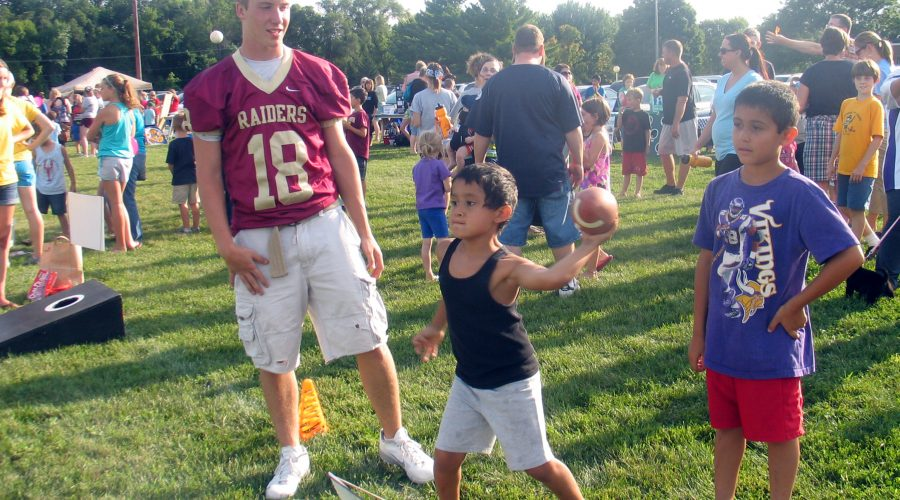 A small boy throws a football with his young friend looking on. A older boy with a football jersey stands by, instructing the boy on how to throw.