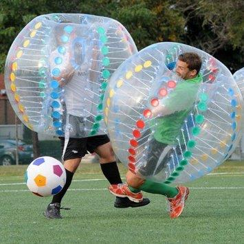 Two men playing bubble-ball soccer on a grass field