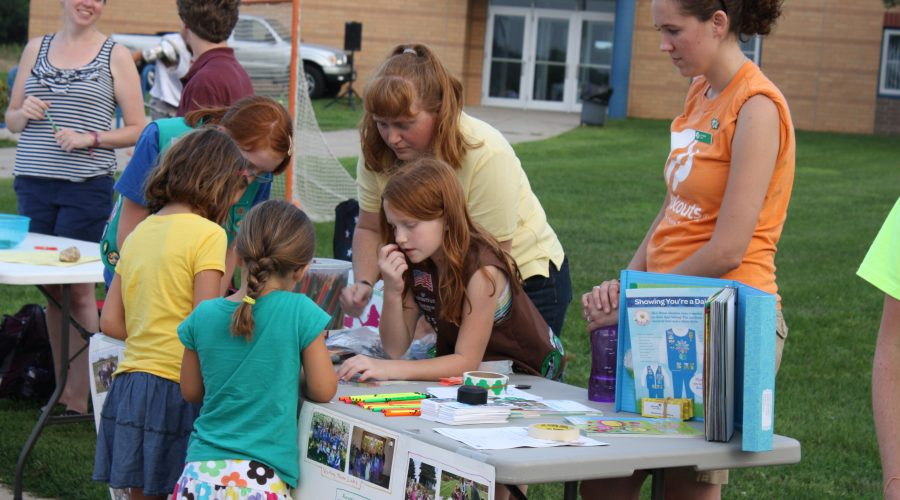 Students and parents man a few tables boasting registration for activities at the Community Youth Fair.