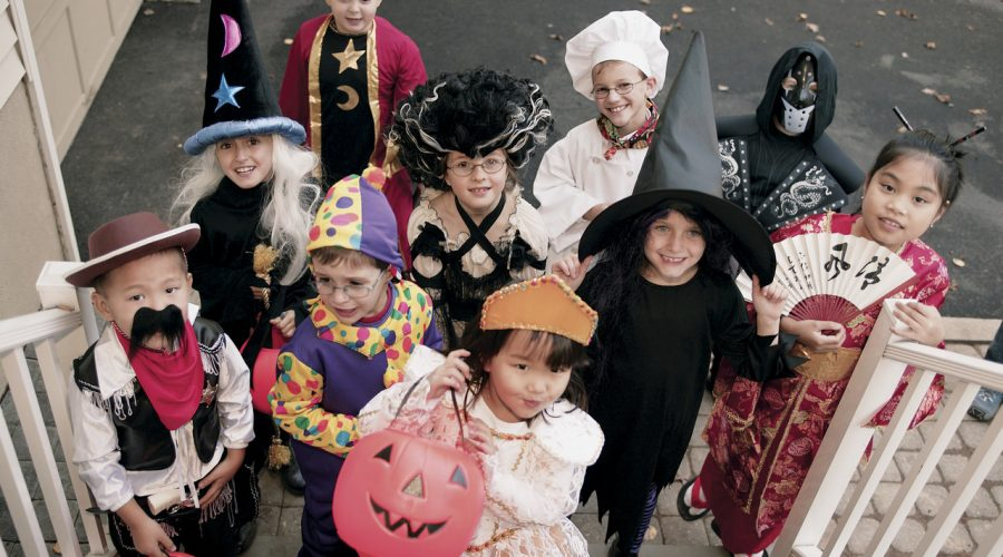 A handful of younglings gather outside dressed in full costume for Halloween.