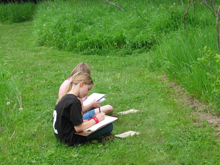 Two students sit drawing in the grass