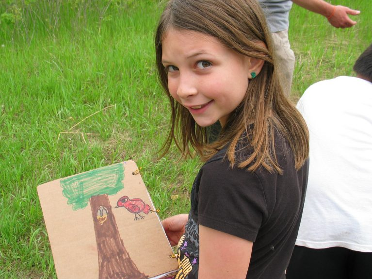 A girl stands in the grass with a drawing of a tree