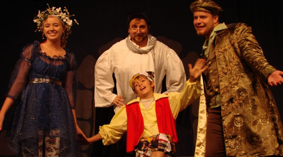 A picture of three adult actors and one child actor dressed in medieval regalia performing Pinocchio.